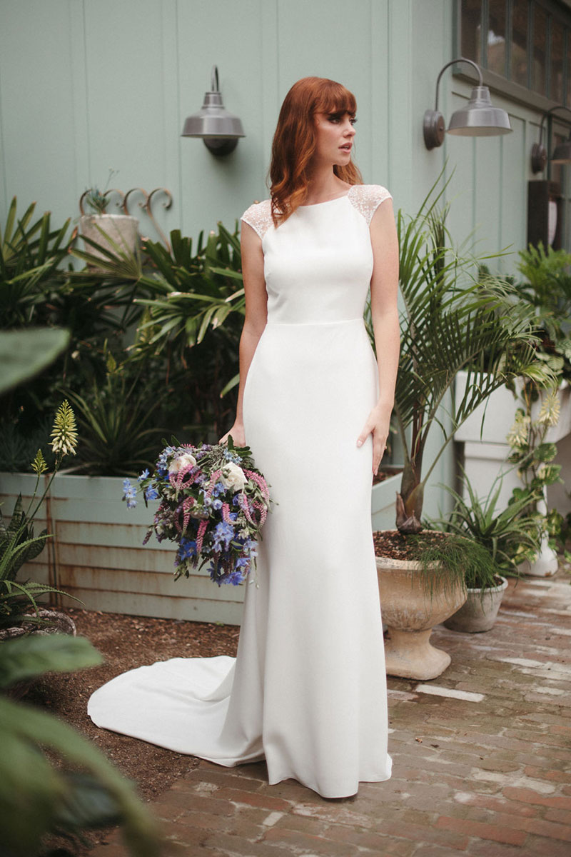Red haired bride holding blue flowers wearing a sleek wedding dress.