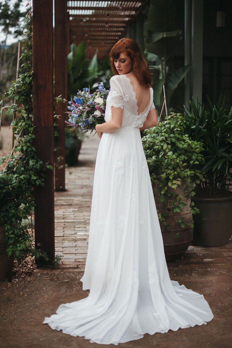 Red haired bride holding flowers in a flowing wedding gown.