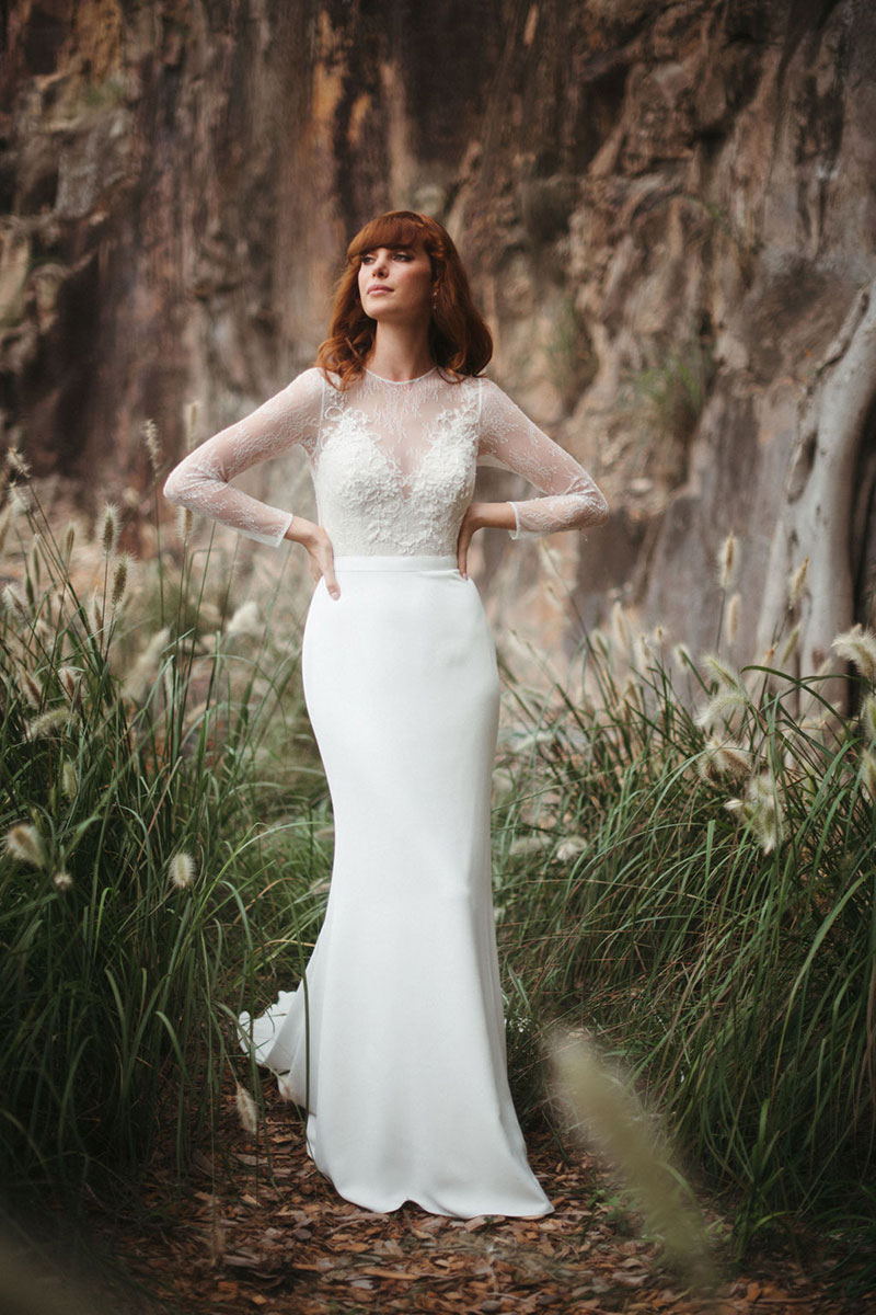Red haired bride wearing a long sleeved wedding dress in outside location.
