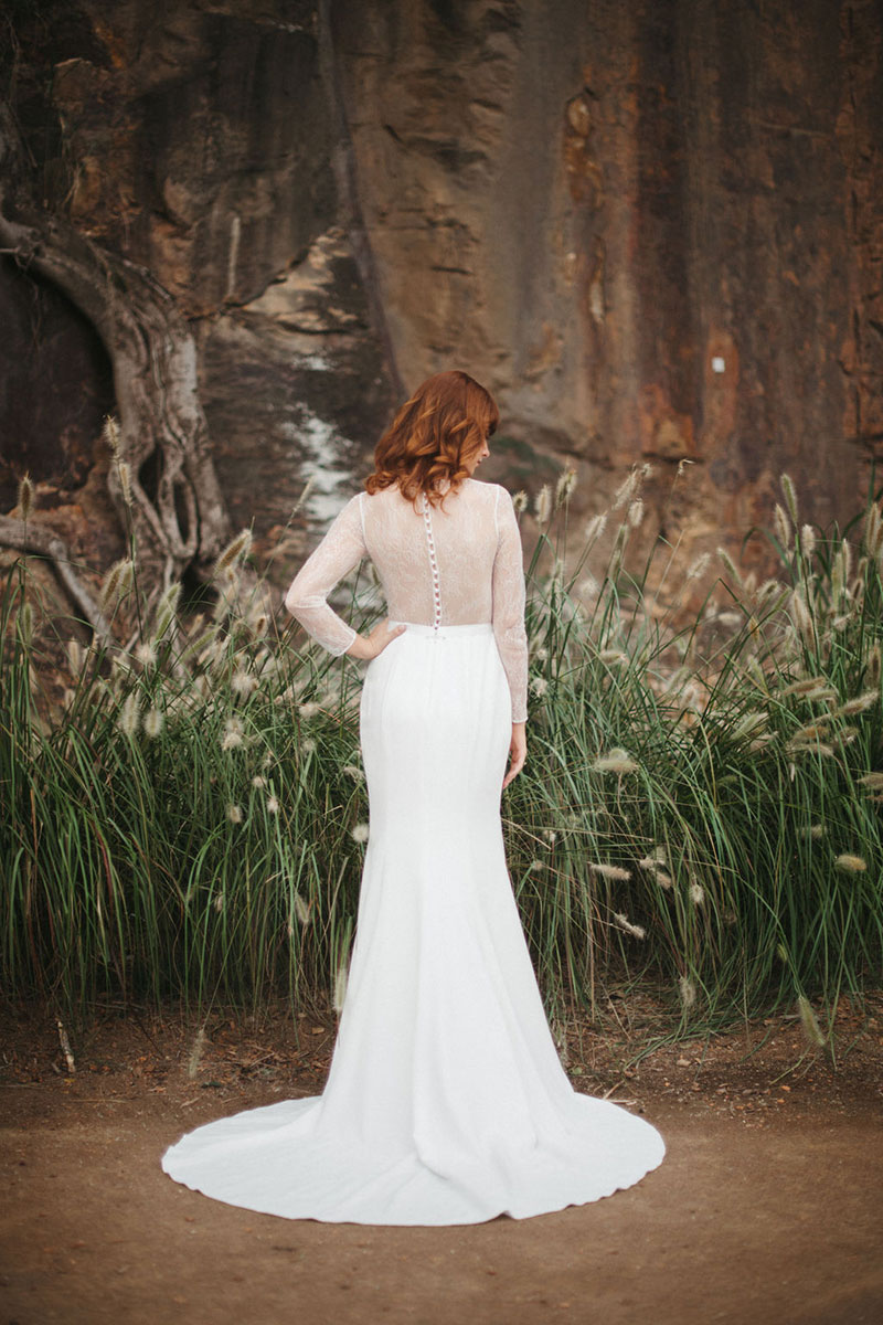 Back view of a long sleeved wedding gown with a circular train.