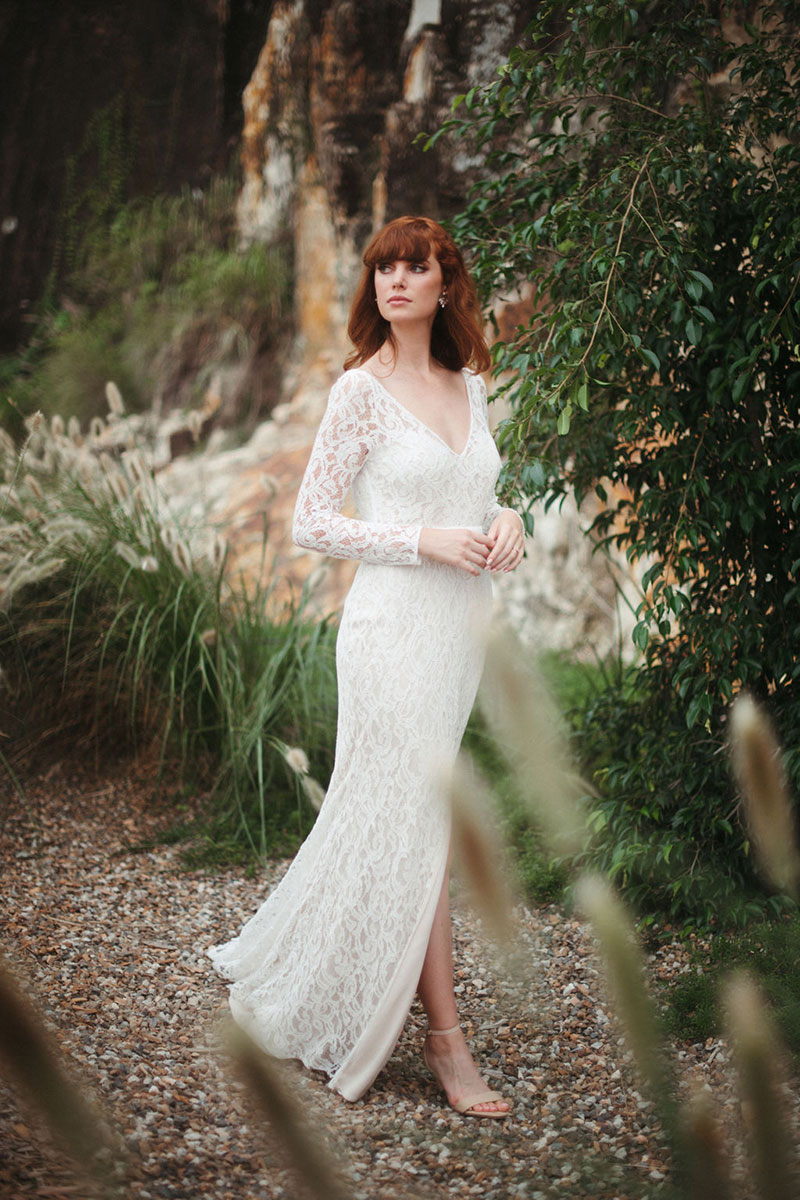 Lace gown worn by red haired bride in outdoor setting.