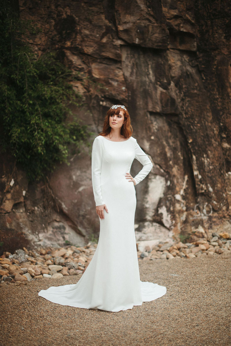 Bride in outside setting wearing a long sleeved wedding gown.