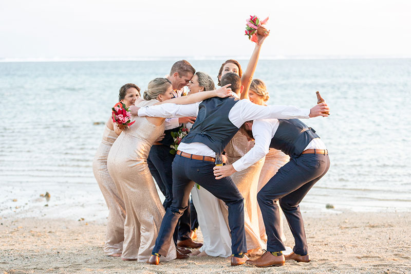 Wedding party grouped together on the beach.