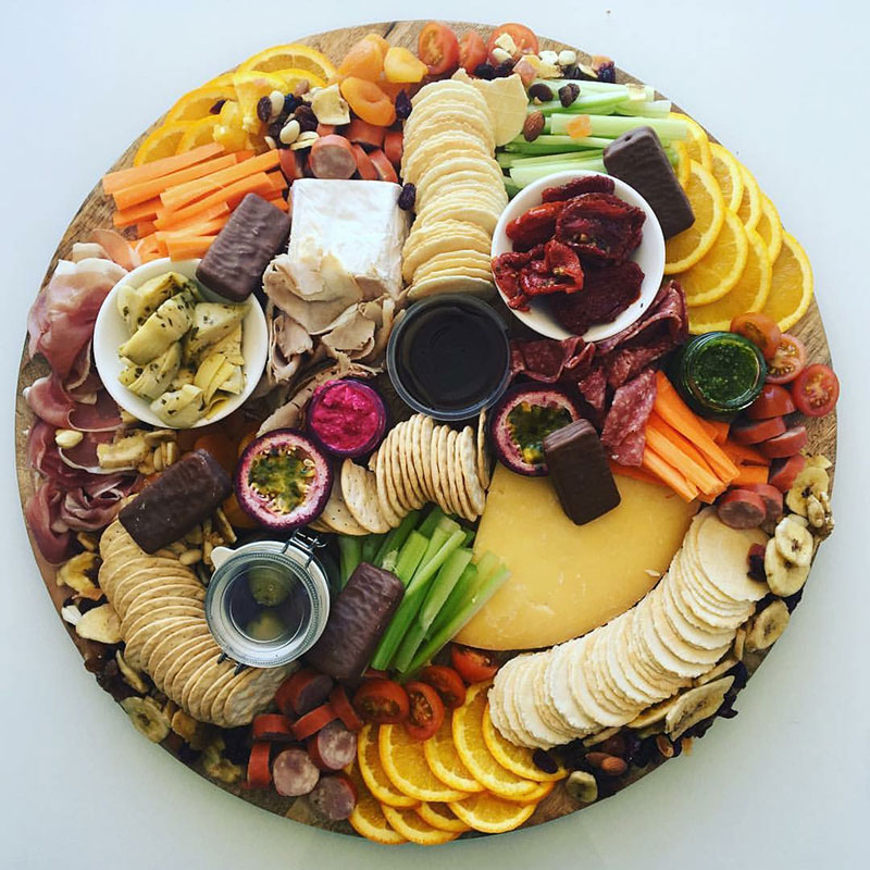 Round Grazing platter board with an assortment of food.