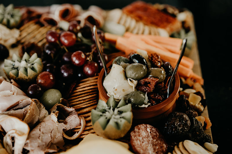Close up of a grazing board with antipasta, kiwi fruit and more.