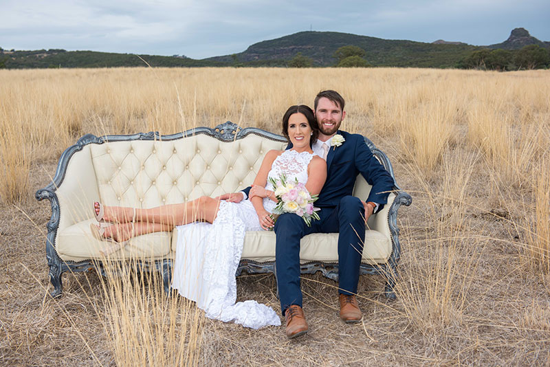 Bride and groom on vintage chair in a field.