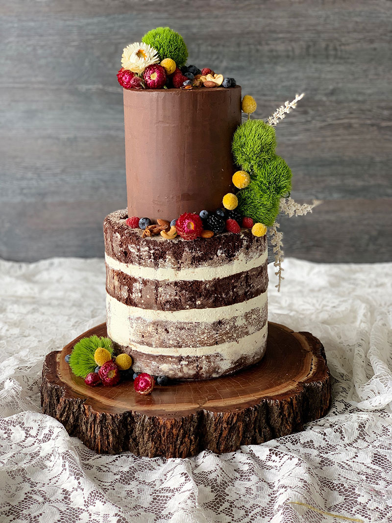 Rustic wedding cake with fruits, nuts and greenery.