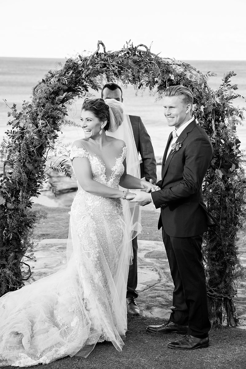 Bride and Groom at a beach wedding looking happy and relaxed during ceremony.