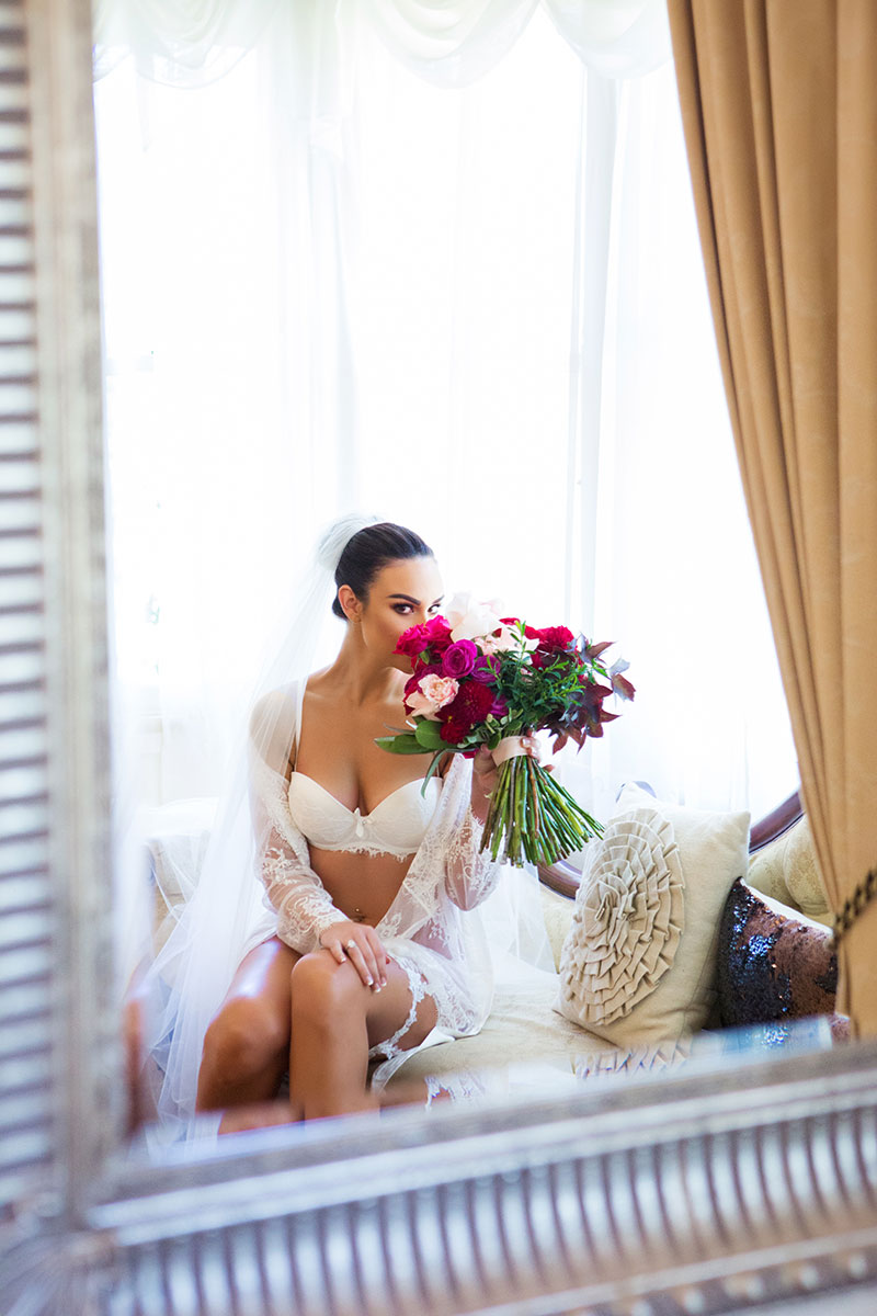 Bride in lingerie and holding flowers while seated.