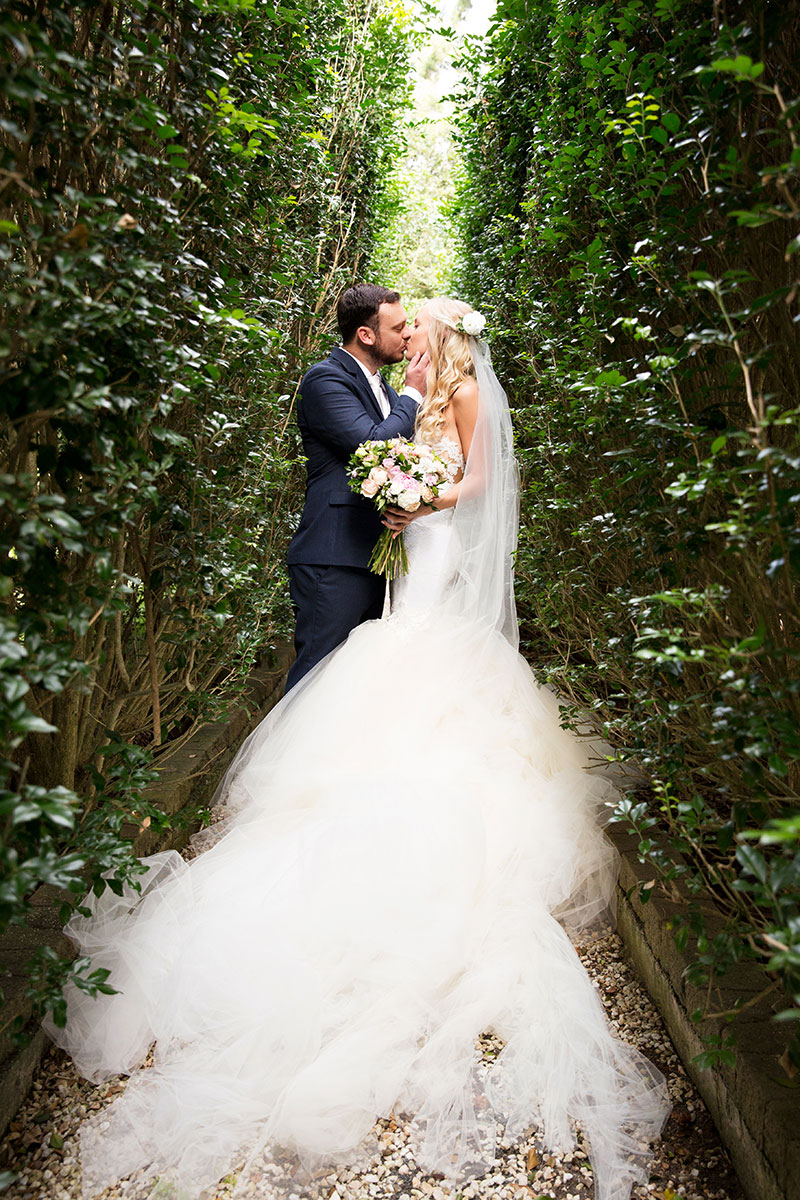 Bride and Groom kissing between tall hedges.