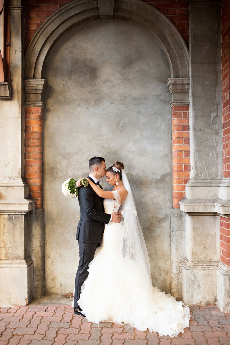 Bride and Groom facing eachother in front of an old brick and concrete wall.