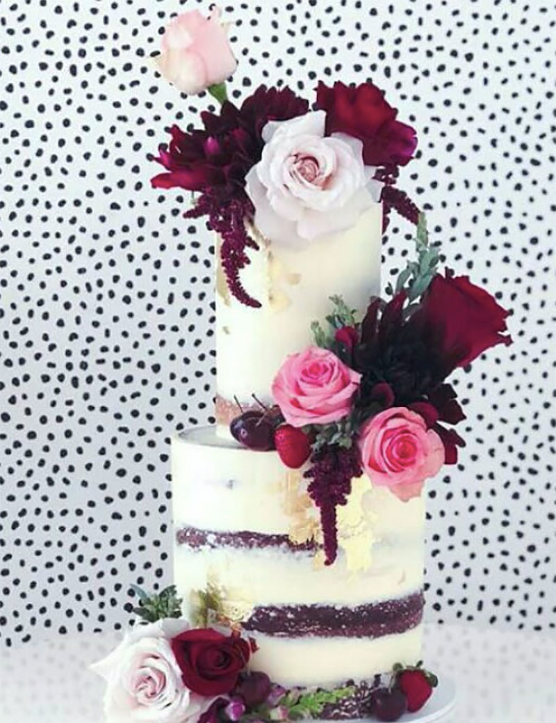 Rustic wedding cake with striking deep red florals.