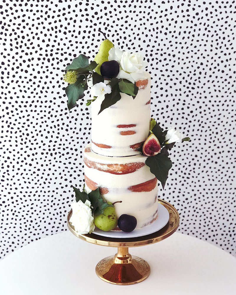 Rustic Wedding cake with crisp greens and seasonal fruits.