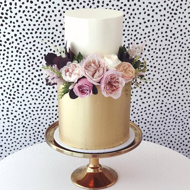 Metallic gold lustre wedding cake with flowers.