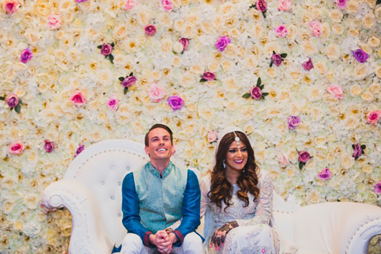Multicultural Bride and Groom sitting together on a white couch in front of a flower wall.