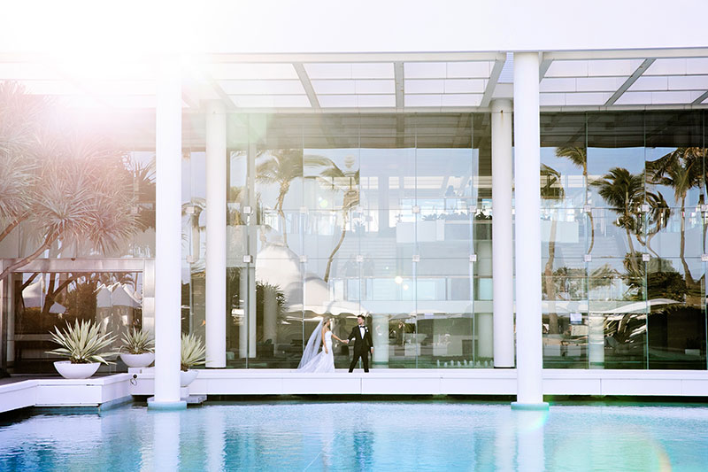 Bride and Groom walking by the pool at Sheraton Grand Mirage Resort, Gold Coast.