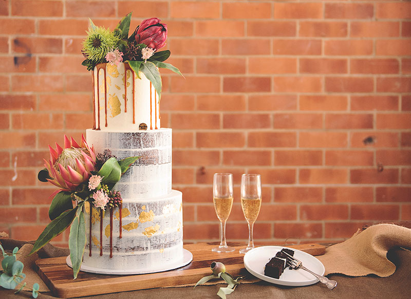 Rustic semi-naked wedding cake with native florals.