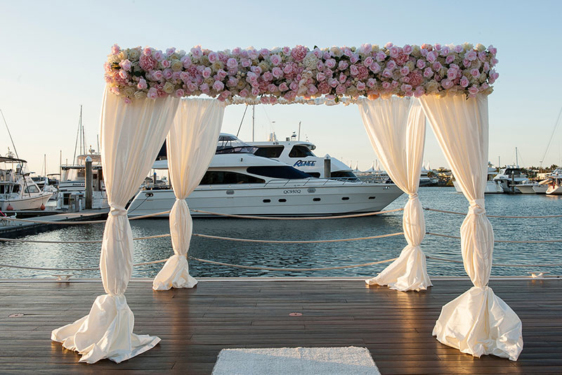 Wedding ceremony arbour set up at Southport Yacht Club with a view of the Marina..