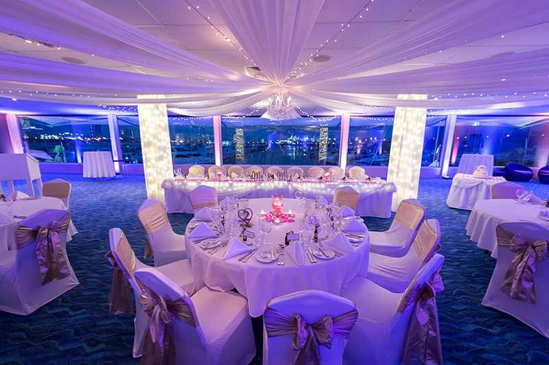Southport Yacht Club set up for a wedding reception with purple lighting.
