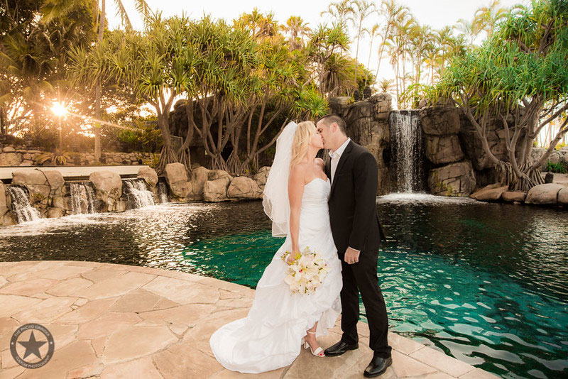 Bride and Groom kissing in front of the pool at Surfers Paradise Marriott Resort & Spa.