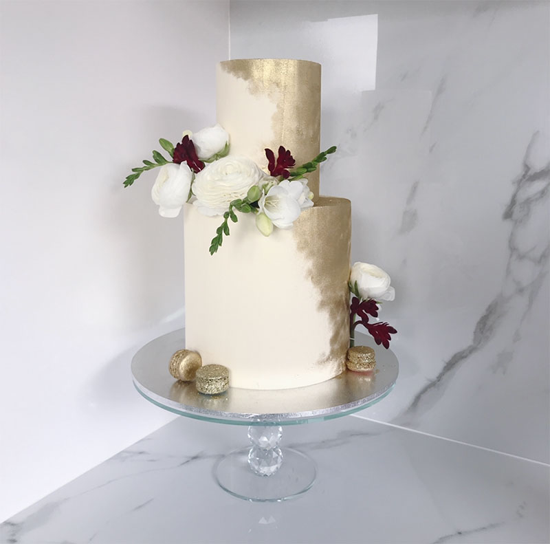 Metallic wedding cake with painted on gold, gold macaroons and flowers.