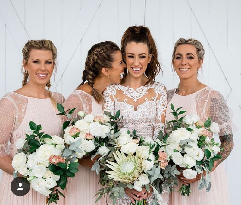 Bride and bridesmaids with classic and native flower wedding bouquets.