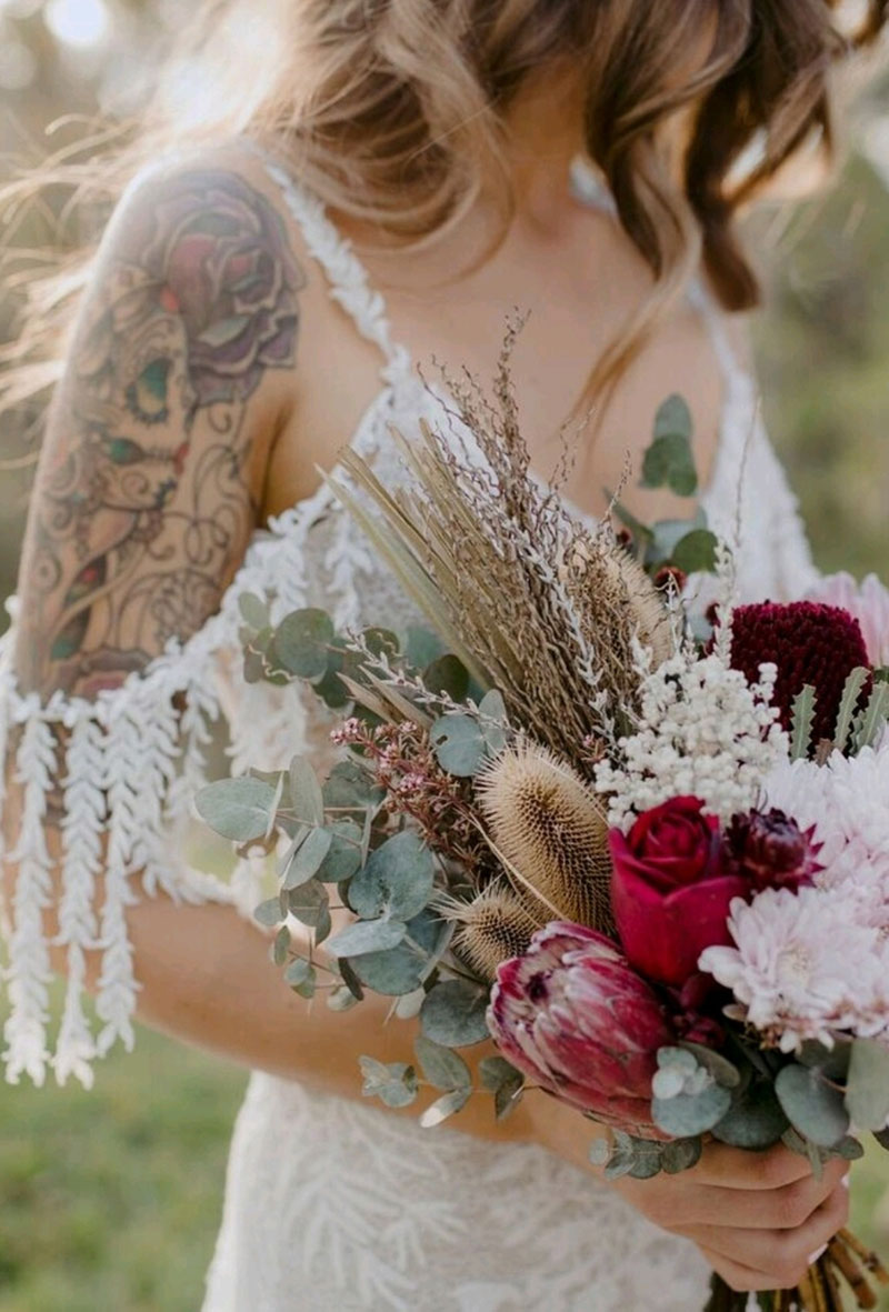 Boho bride holding a wedding bouquet of dried and native flowers.