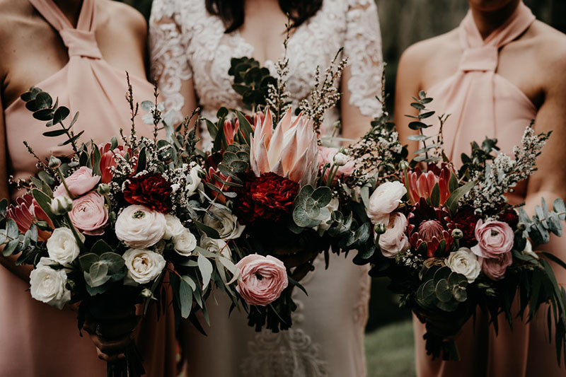 Bride and bridesmaids holding deep, rich wedding flower bouquets.
