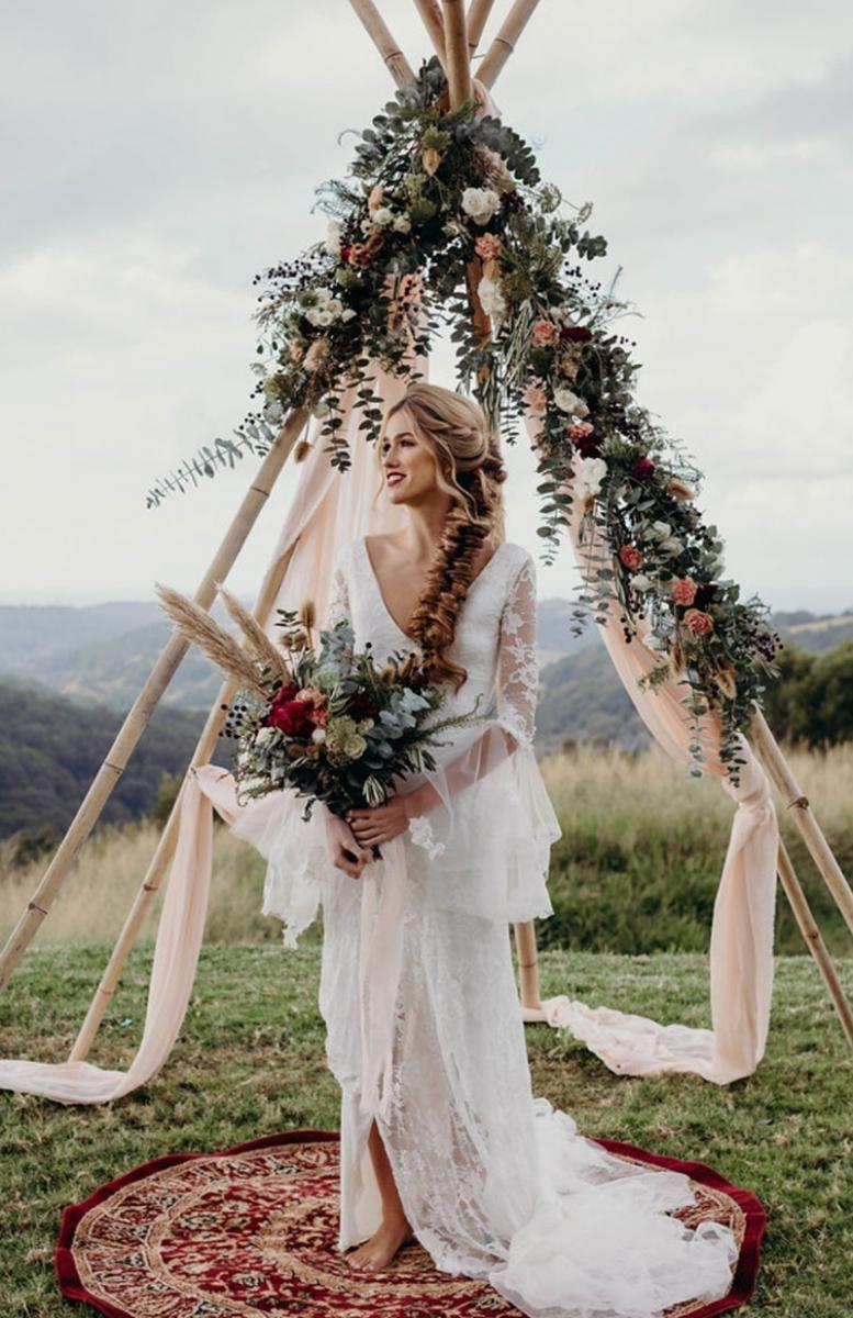 Boho bride holding a gorgeous bouquet in front of an arch with hanging flowers.
