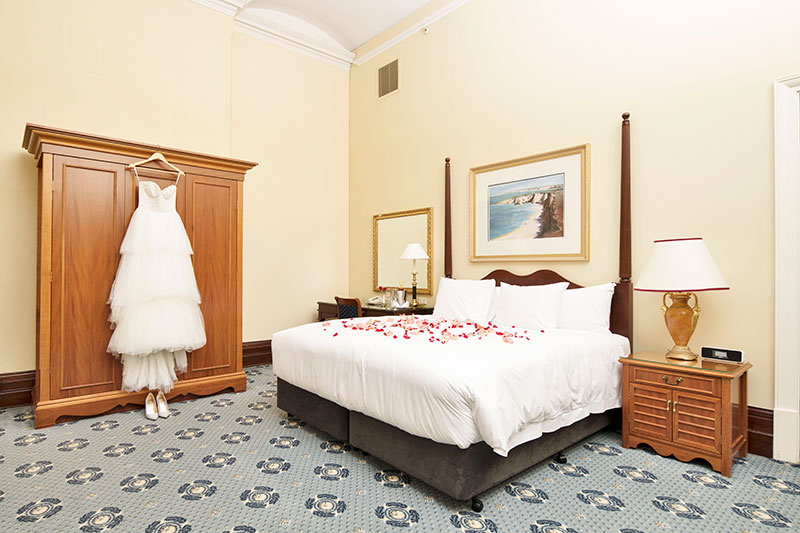 Spacious Deluxe King Room with rose petals on bed at Treasury Brisbane.