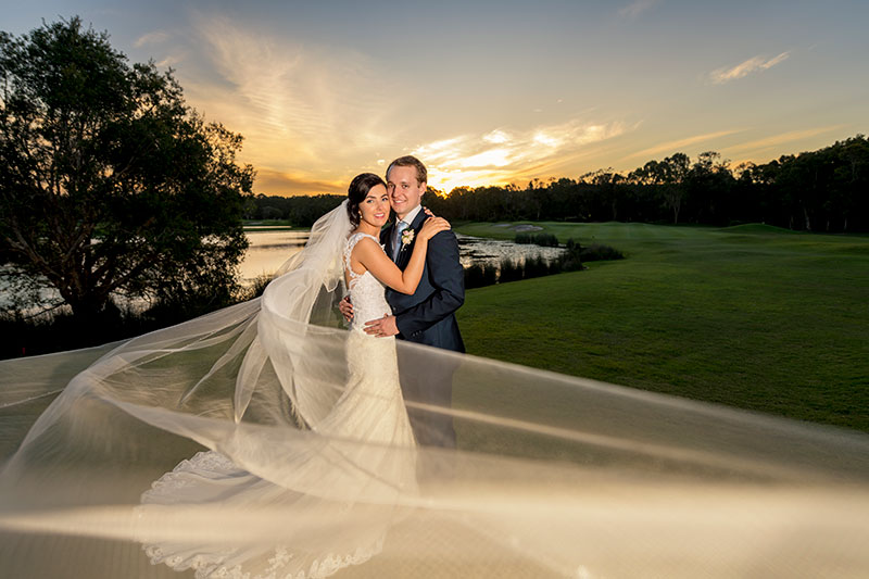 Bride and groom hold each other with a sunset on Twin Waters Golf Club.