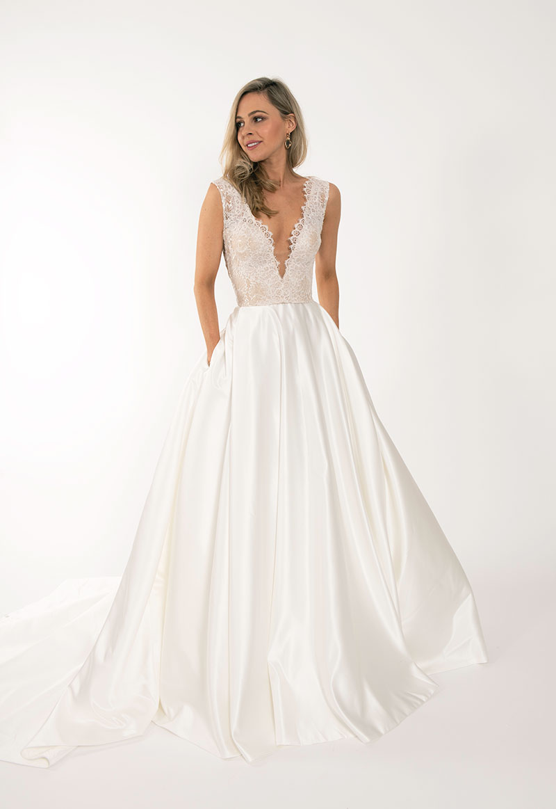 Low-cut fitted bridal bodice with flowing skirt by Q'Nique Exquisite Bridal Wear.