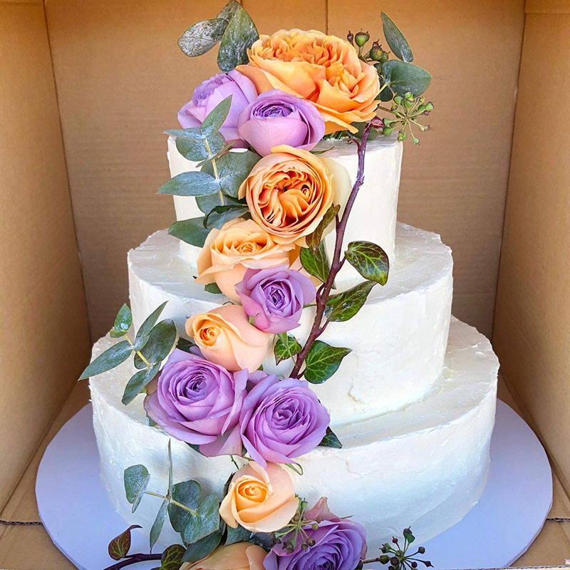 White wedding cake with colourful roses draping it.