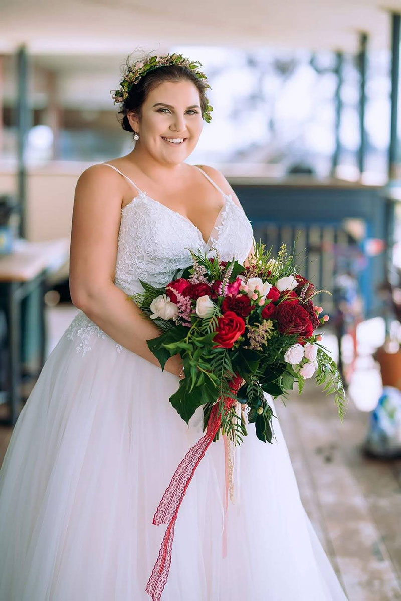 Bride with wedding hair flowers holding a large bouquet.