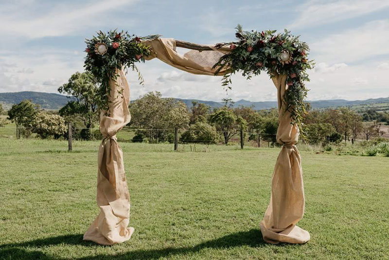 Country styled arbour with artificial native wedding flowers.