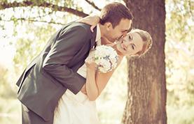 Groom bending over to kiss Bride.