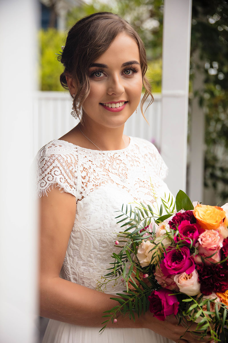 Bride smiling holding big bouquet of flowers.