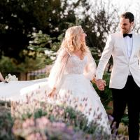 Groom in stylish White jacket and Black bowtie and pants walking with his beautiful Bride in White.