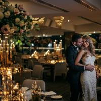 Happy Bride and Groom hold eachother in an opulent function room filled with flowers and tea lights.