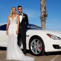 Bride and Groom standing in front of a Maserati.