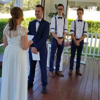 Bride and Groom getting married with two young groomsmen looking on