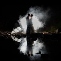Photo of couple at night standing in front of a light and smoke bomb.