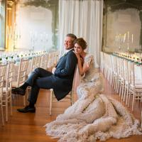Bride in extravagent wedding gown poses with Groom inside an exquisite reception room.