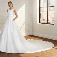 Model posing in room, wearing a crisp white bridal gown from Rosa Clara.
