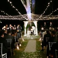 Outdoor wedding ceremony under fairylights at night.