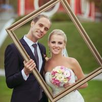Bride and groom holding picture frame