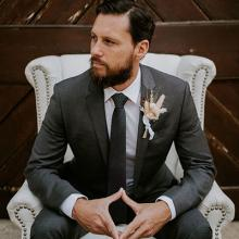 Groom sitting in white chair wearing a grey suit from Black Jacket Suiting.