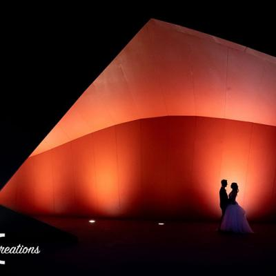 Bride and Groom stand in front of a lit up red coloured structure.