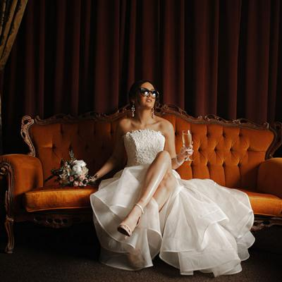 Photo by Tom Judson Photography of Bride with sunglasses and champagne in hand sits on ornate red sofa.