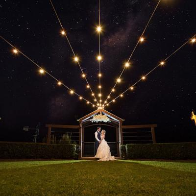 Bride and groom at night with lights at Flaxton Gardens.